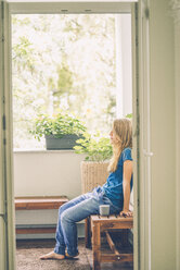 Relaxed young woman sitting on balcony with cup - KNSF01675