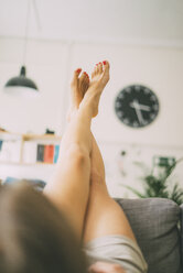 Legs of woman lying on couch at home - KNSF01684