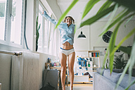 Excited young woman jumping at home - KNSF01690
