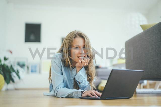 Portrait of young woman lying on floor using laptop - KNSF01693