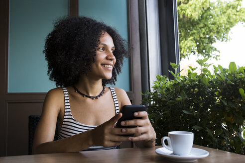 Young woman with smartphone sitting in a coffee shop looking out of window - ABZF02147