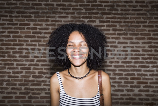 Portrait of smiling woman with eyes closed in front of brick wall - ABZF02159