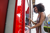 Smiling woman pushing credit card at cash dispenser - ABZF02165
