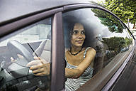 Woman driving a car looking out a car window - ABZF02168