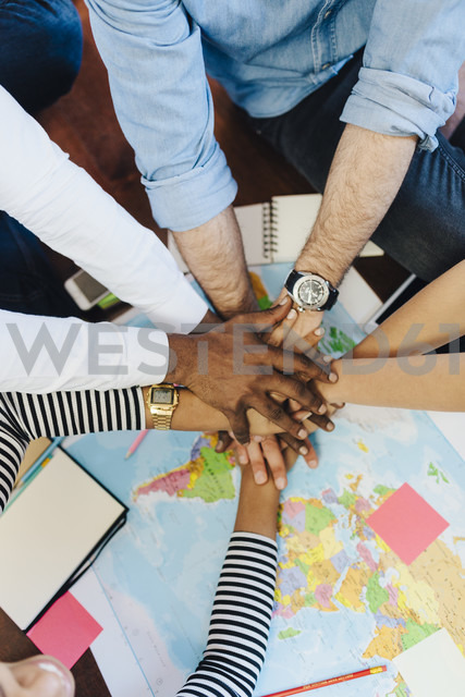 Group of friends stacking hands above world map - GIOF02809