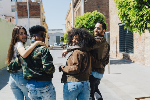 Happy stylish friends walking on urban street - GIOF02818