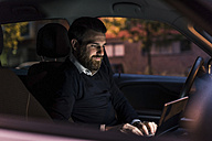 Businessman using laptop in car at night - UUF10878