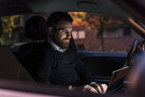 Businessman using laptop in car at night - UUF10878