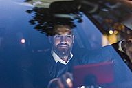 Businessman using navigation device in car at night - UUF10881