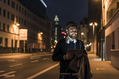 Stylish young man with tablet on urban street at night - UUF10884