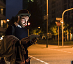 Stylish young man with tablet on urban street at night - UUF10887