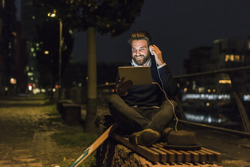 Smiling young man with tablet and headphone in the city at night - UUF10890