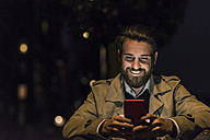 Smiling young man with cell phone in the city at night - UUF10896