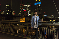 Young man with tablet and earphone on urban bridge at night - UUF10902