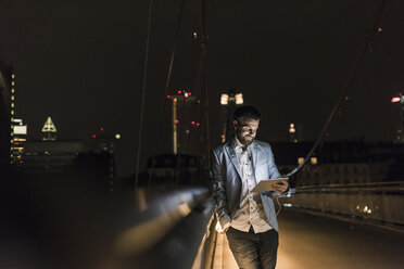 Young man with tablet and earphone on urban bridge at night - UUF10905