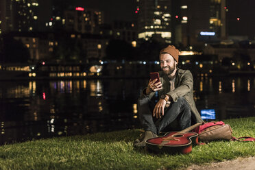 Smiling young man with guitar and cell phone sitting at urban riverside at night - UUF10911