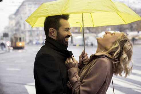 Happy business couple under umbrella in the city - MAUF01110