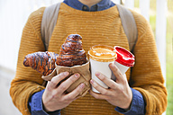 Young man with croissant and coffee to go - RTBF00938
