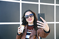 Portrait of smiling young woman with coffee to go taking selfie with smartphone - RTBF00950