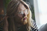 Portrait of man with long blond hair wearing spectacles - RTBF00953