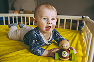 Portrait of baby boy with wooden toy lying in his crib - MFF03676