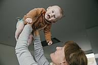 Grandmother lifting up baby at home - MFF03679