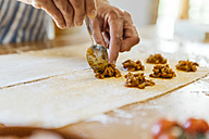 Woman's hands putting ravioli stuffing on dough - JRFF01402