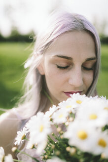Woman with eyes closed holding bunch of daisies - GIOF02823