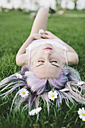 Woman lying on grass with flowers on hair - GIOF02838
