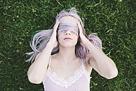 Woman lying on grass covering eyes with her hair - GIOF02841