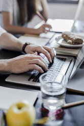 Hands of man using laptop at home - GIOF02849