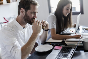 Man eating and woman using laptop at home - GIOF02852