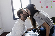 Happy couple with laptop at home kissing - GIOF02864
