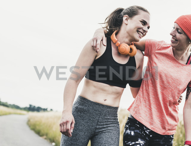 Two happy women having a break from exercising - UUF10927