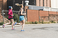 Two women running on the street along factory building - UUF10933
