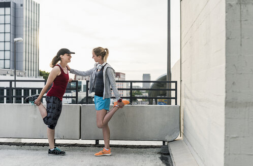 Two active women stretching in the city - UUF10939