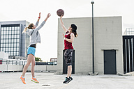 Two women playing basketball on parking level in the city - UUF10942