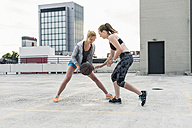 Two women playing basketball on parking level in the city - UUF10948