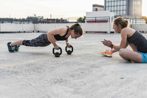 Woman cheering at training partner kettlebell on parking level in the city - UUF10954