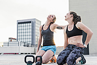 Two women with kettlebells having a break from exercising on parking level in the city - UUF10957