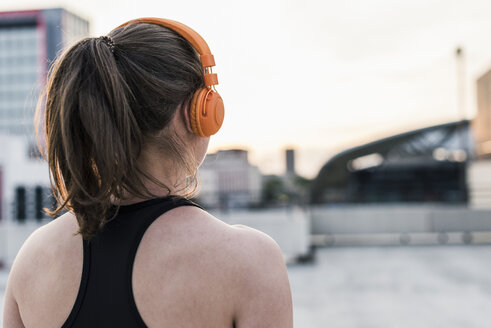 Active woman wearing headphones on parking level in the city - UUF10966