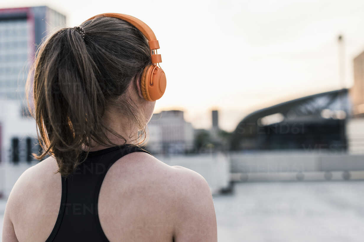 Active woman wearing headphones on parking level in the city - UUF10966 - Uwe Umstätter/Westend61