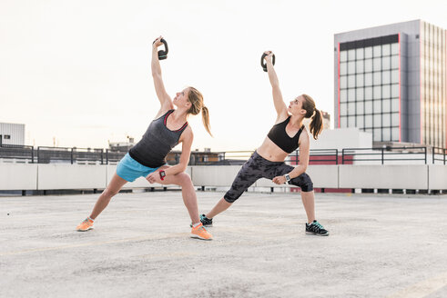 Two women exercising with kettlebells on parking level in the city - UUF10972