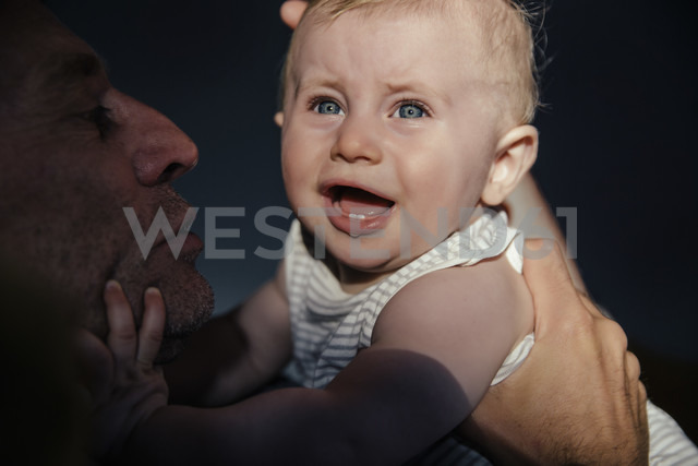 Portrait crying baby boy on his father's arms - MFF03691