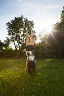 Back view of girl doing handstand on a meadow - LVF06206