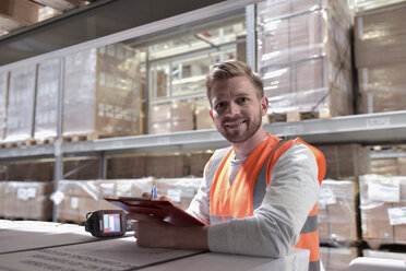 Portrait of smiling man in factory hall wearing safety vest holding clipboard - LYF00736