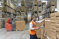 Man  with clipboard in factory hall and moving forklift - LYF00742