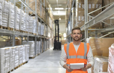 Portrait of confident man in factory hall wearing safety vest holding clipboard - LYF00754