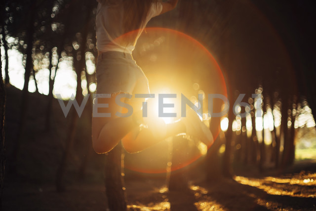 Woman jumping at forest with sunset - JPF00247 - Javier Pardina/Westend61