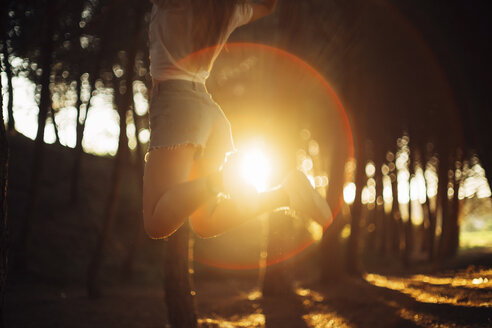 Woman jumping at forest with sunset - JPF00247